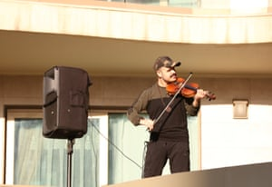 Nujin Hasan, gives a morale concert to the residents of his apartment from his balcony, during the curfew
