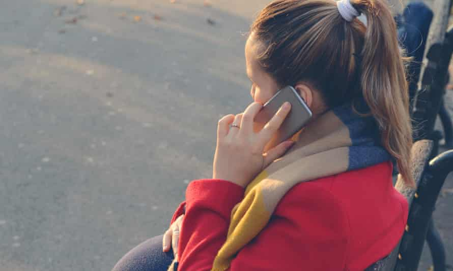 pregnant woman sitting on bench using mobile phone