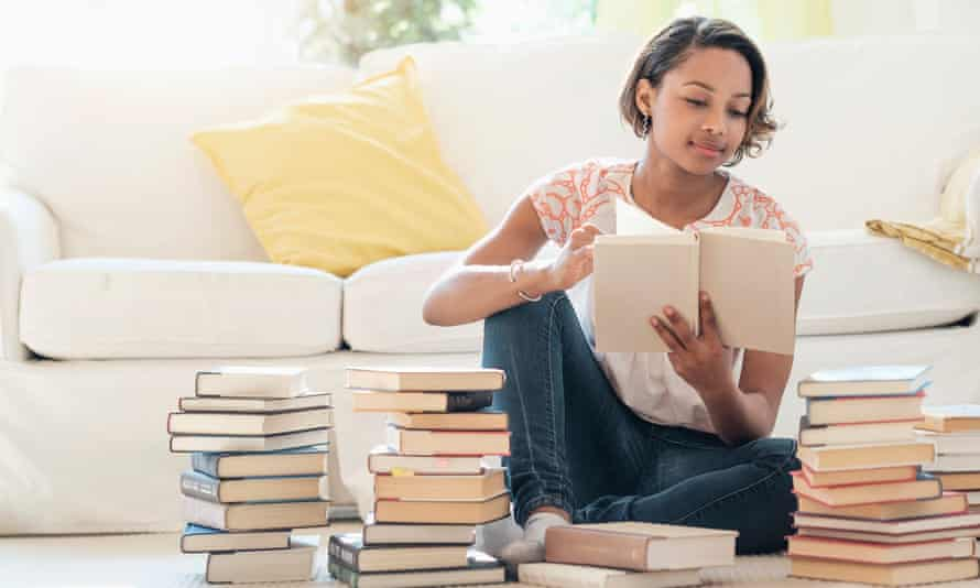 woman sitting on floor reading pile of books