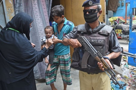 A policeman protects a health worker in Karachi. After a policeman opened fire in Chaman last month, officers in the area are now reluctant to protect female polio workers.