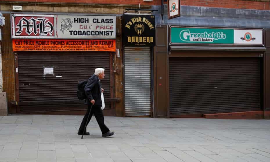 A man walks past closed shops in Rochdale.