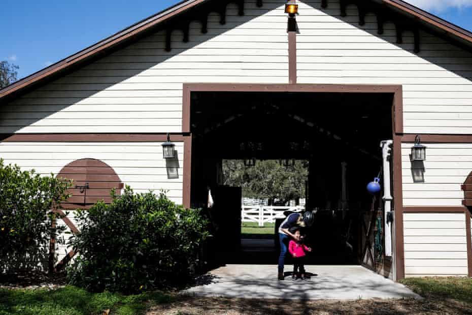 Pastor Paula White-Cain helps her granddaughter, Asher, 2, get a helmet on to go horseback riding at her home in Apopka, Florida on Thursday, February 28, 2019. White-Cain is a senior pastor at New Destiny Christian Center.