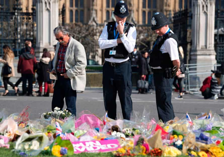 Police officers stop to look at floral tributes to the victims near the Houses of Parliament in Westminster.