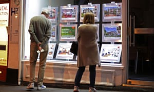 People view proporties in an estate agent's window