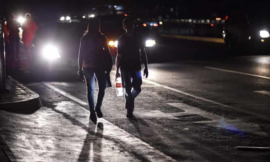 A couple walks along a street in darkness.