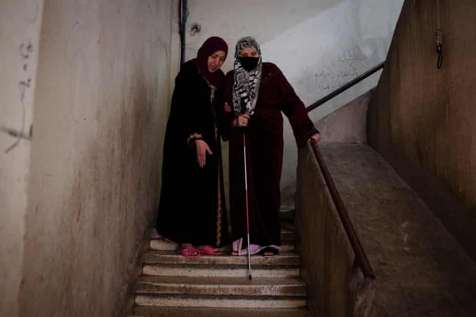 Ahlam (left), 65, helps her sister Aydah, 69, down the stairs in their apartment block in Beirut
