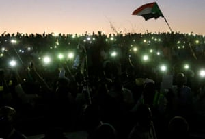 Demonstrators use their mobile phone torches as lamps as they attend a mass anti-government protest outside the defence ministry in Khartoum, Sudan