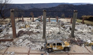In a December photo, a vehicle rests in front of a home leveled by the Camp Fire in Paradise, California.