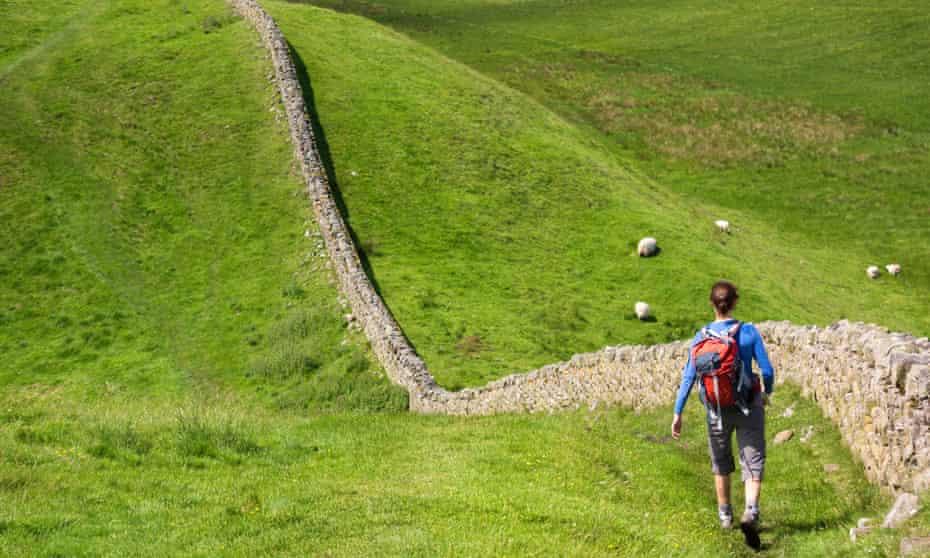 Hiker walking alongside Hadrians Wall