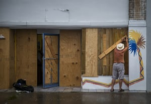 A man boards up his property in preparation for Hurricane Harvey's landfall in Aransas Pass, Texas