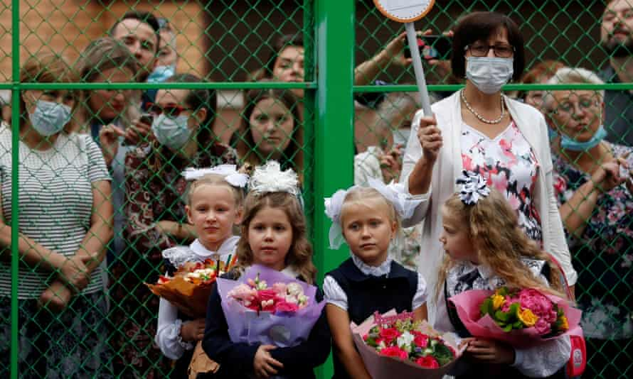 A teacher wears a face mask as she stands next to first graders during a ceremony in Moscow last month marking the start of the new school year