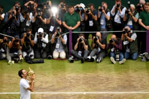 Roger Federer of Switzerland celebrates victory with the trophy as he poses for photographers.