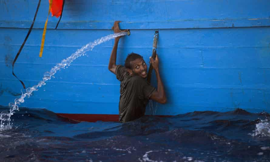 A man holds himself to the side of a boat