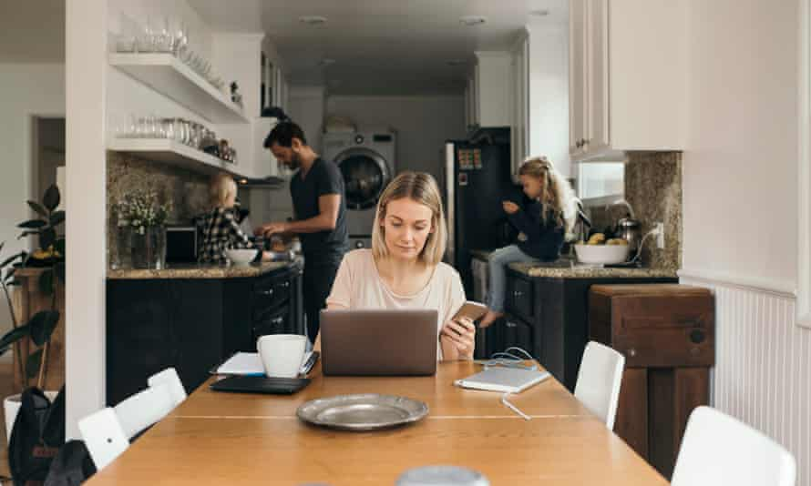 Woman using laptop at table with family in kitchen at home