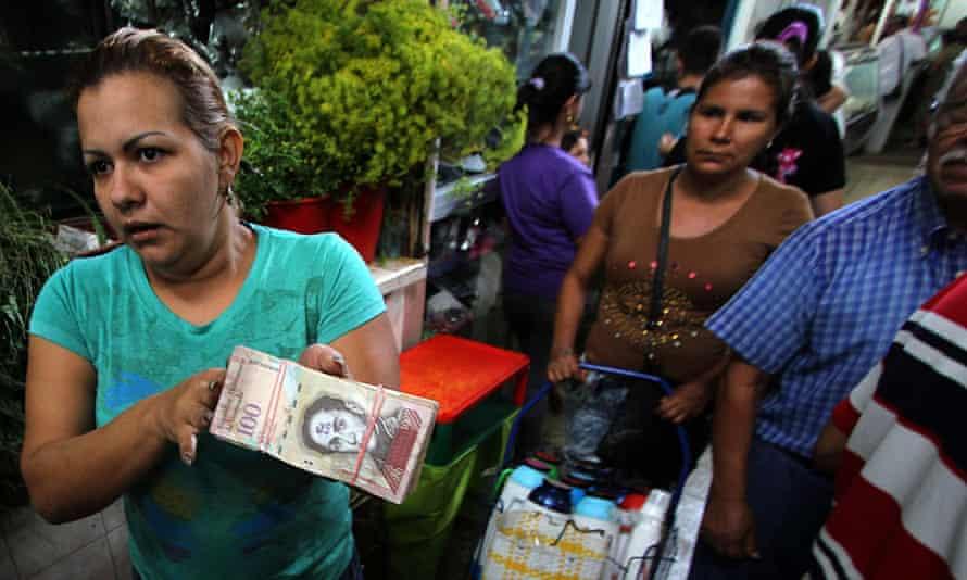 A woman shows a wad of 100-bolivar bills in San Cristobal, Venezuela