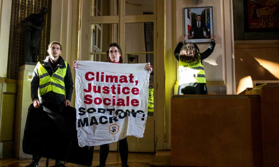Climate activists remove a portrait of President Macron from a French government building