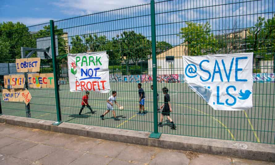 Protest banners on display as local children play in Bells Gardens, Peckham, south London.