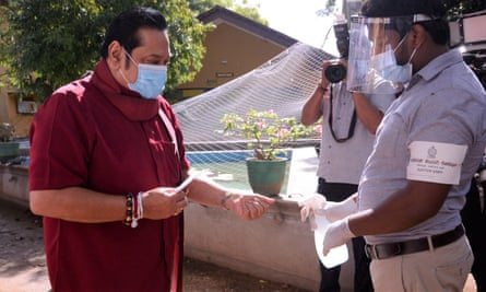 Sri Lankan Prime Minister Mahinda Rajapaksa sterilises his hands before voting. His party is on course for a landslide win in the country's election.
