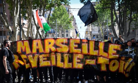 Protesters hold a banner that reads 'Marseille wake up'.