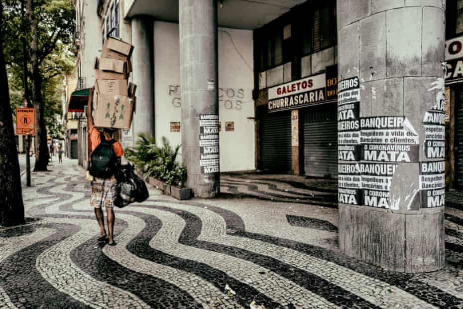A man walks next to a poster in Rio Centro that reads: 'Bankers, respect the lives of workers and customers – coronvirus kills'