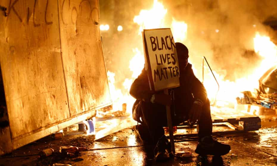 A demonstrator sits in front of a street fire following the grand jury decision in the Ferguson, Missouri shooting of Michael Brown, in Oakland, California, 25 November 2014.