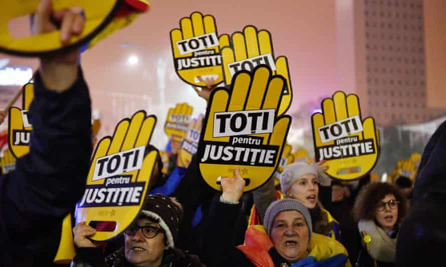 People hold placards reading: 'All for justice' during a protest against the Romanian government and corruption in Bucharest.