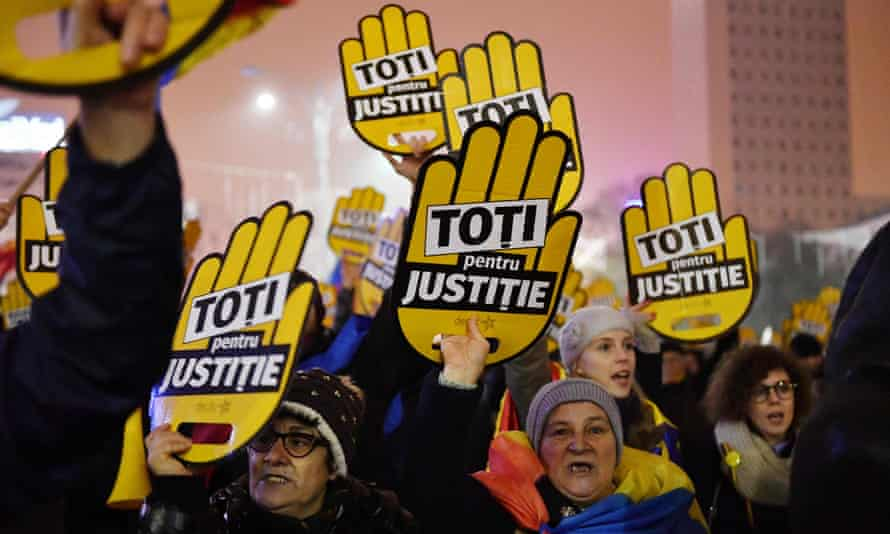 People hold placards reading 'All for justice' during a protest in Bucharest