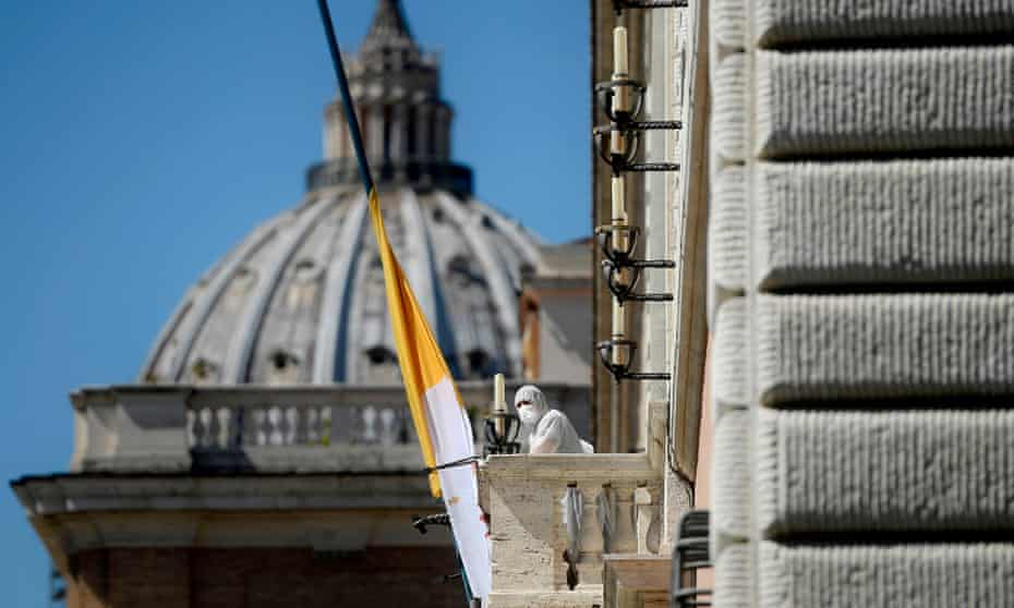 A person in protective gear stands at the balcony of a Vatican building on Via della Conciliazione in Rome