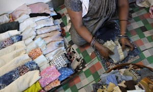 A worker makes recyclable sanitary cloth napkins in Madanpur Kheri