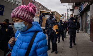Police officers walk along a street handing out information leaflets advising how to report on hate crimes, at a park in Chinatown, New York City on March 17, 2021.