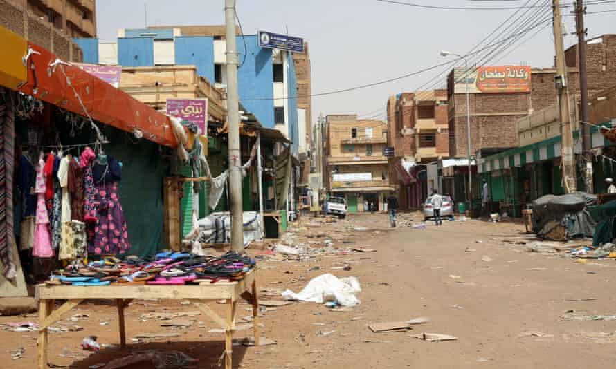 People walk down a mostly empty street in Omdurman, Sudan