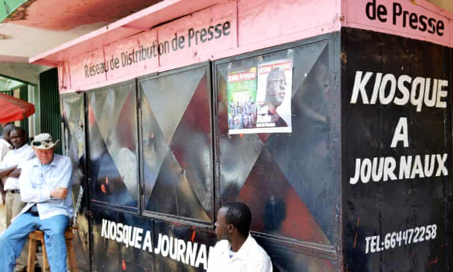 Men sit in front of closed newspaper stand