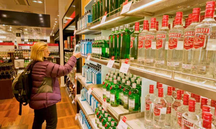 Woman traveller shopping for duty free alcohol in an airport duty free shop