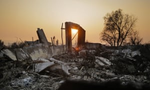 The sun sets through smoke over the remains of homes in the Fountaingrove neighborhood in Santa Rosa.