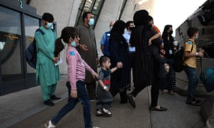 People evacuated from Kabul wait to board a bus that will take them to a refugee processing center at the Dulles international airport in Virginia today.