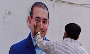 A protester puts his hand on the face of a cutout of Nirav Modi during a demonstration in New Delhi in February 2018