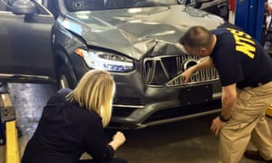 Investigators examine a driverless Uber SUV that fatally struck a woman in Tempe, Arizona.