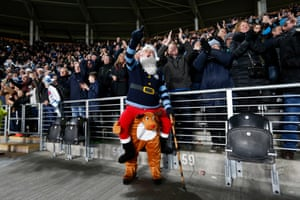 A festive Manchester City fan and his less fancily dressed fellow fans celebrate during City's 3-0 away win over Hull City