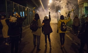 Protesters hold flowers as police fire teargas during an anti-regime protest in front of Tehran's Amir Kabir University on Monday.