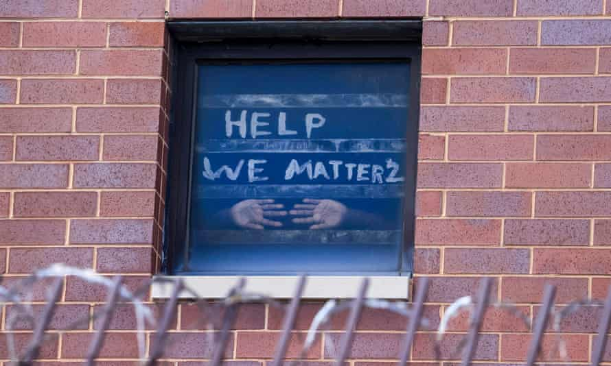 An inmate in the maximum security unit of the Cook County Jail presses his hands against the window below a plea for help in Chicago on 10 April.