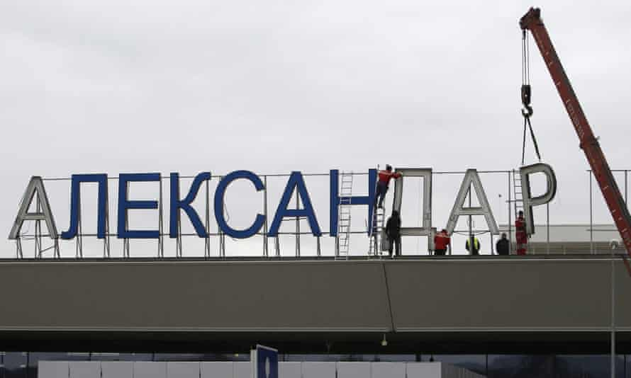 Workers removing the sign saying 'Alexander the Great airport' in Skopje in February.