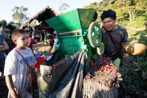Tankoari villagers pass the coffee beans through a grinder, which strips off the skin