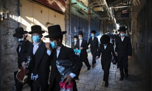 A group of ultra-Orthodox Jewish youth wear protective face masks following government measures to help stop the spread of the coronavirus, as they walk in Jerusalem's Old City on Thursday.