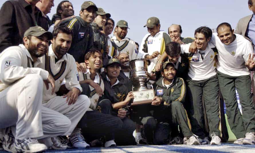 Pakistan's cricketers surround the winning trophy after beating England following the third Test in Lahore in December 2005.