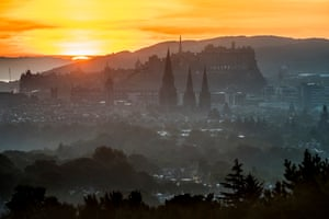 "Edinburgh, Scotland: A view from ""Rest and be Thankful"" of a misty Edinburgh castle and the Salisbury Crags in the early morning."