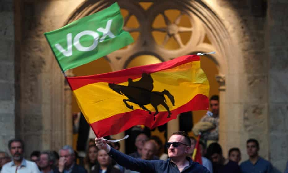 A man waves a Vox party flag and a Spanish flag at a campaign rally in Burgos, northern Spain.