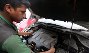 A mechanic repairs a VW car in India, where the company will recall 324,000 diesel vehicles.