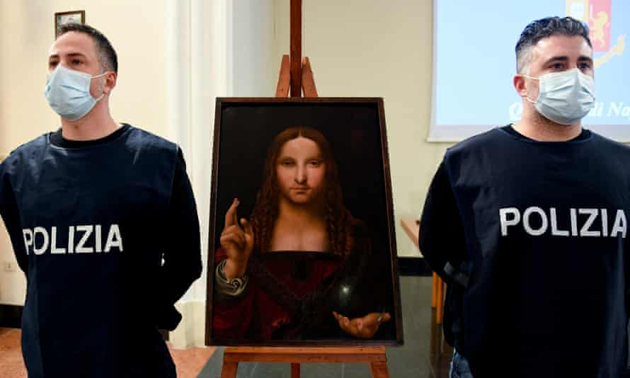 Police officers stand next to the recovered Salvator Mundi painting