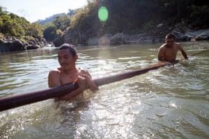 Lenca men retrieve part of a bridge in the Gualcarque river at Río Blanco, Intibucá