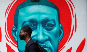 Man wearing a protective mask walks past a mural of George Floyd  in Chicago, the US, on 27 July.